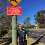 Ricardo Lonza under one of the new signs on Ben Lomond Road, Minto Heights