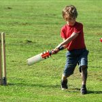 action shot of boy playing cricket