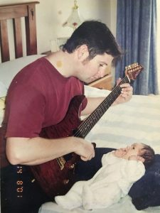 Mr Warren playing his guitar to son Bailey and a flyer from a gig Mr Warren played in 2001, below.