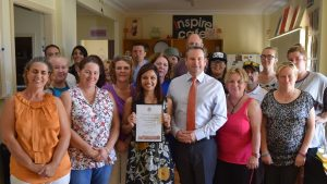 MP Greg Warren presents a certificate to One Door Harmony House for 10 years of service in Campbelltown.