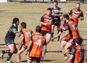 a Magpies player is surrounded by a wall of Tigers defenders.